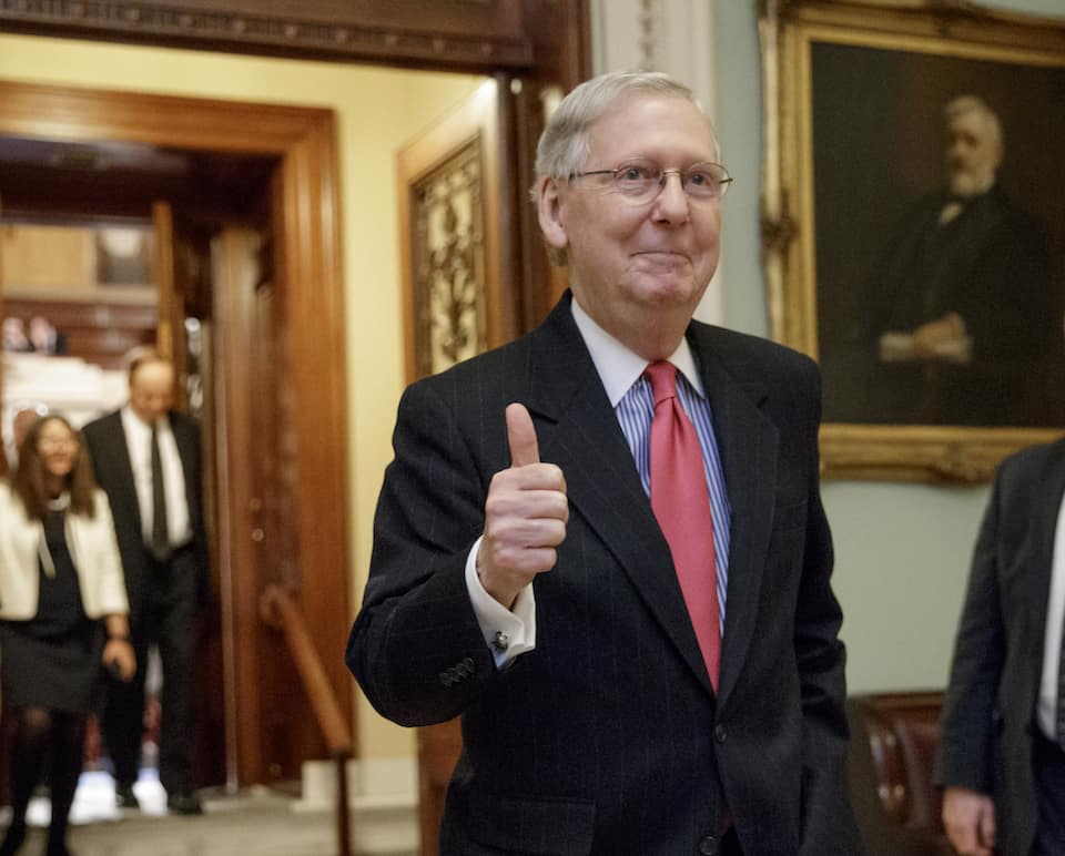Photo of Mitch McConnell walking in hallway giving a thumbs up