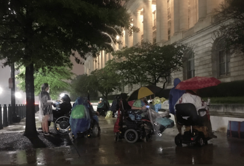 Activists sit in the rain outside the Capitol to protest cuts to Medicaid