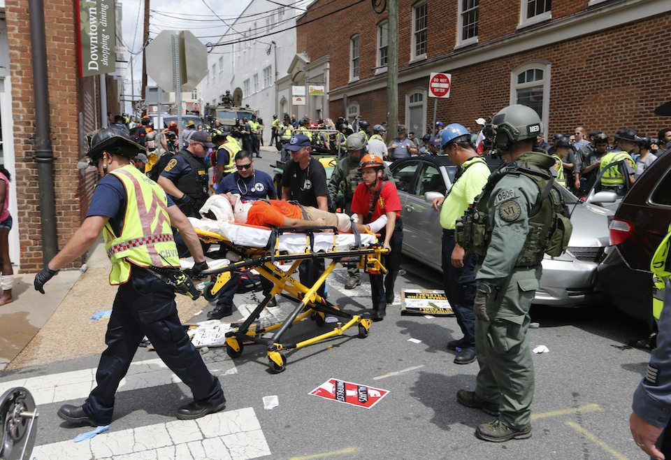 Rescue personnel help injured people after a car ran into a large group of protesters after a white supremacist rally in Charlottesville, VA
