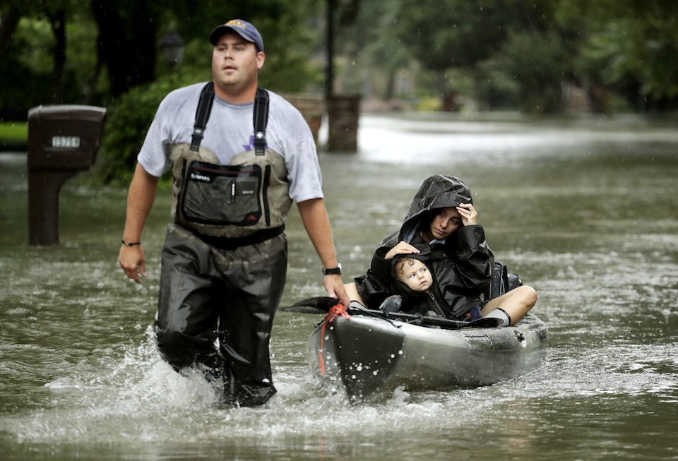 People evacuate a neighborhood in west Houston inundated by floodwaters from Tropical Storm Harvey