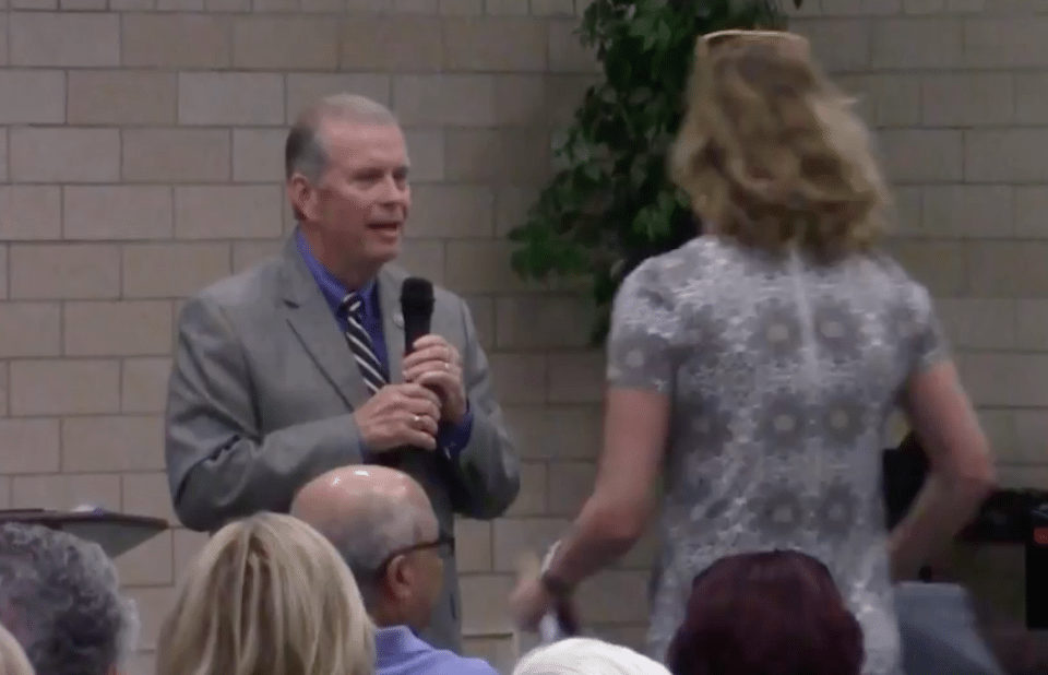 A woman walks out of Michigan Republican Rep. Tim Walberg's lie-filled town hall