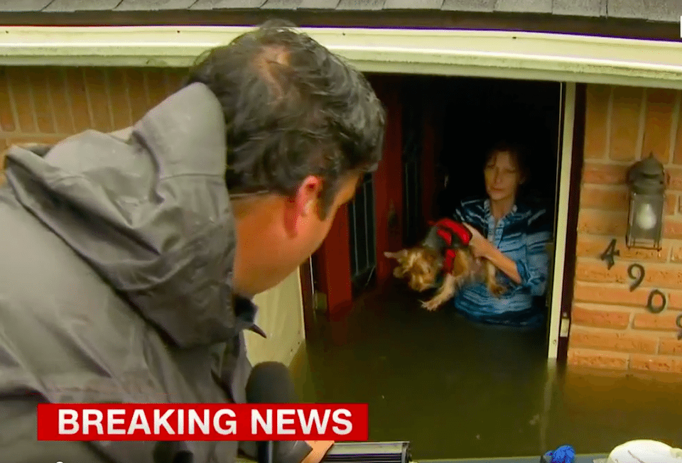 CNN reporter Ed Lavandera helps a woman and her dog escape their flooded Houston home