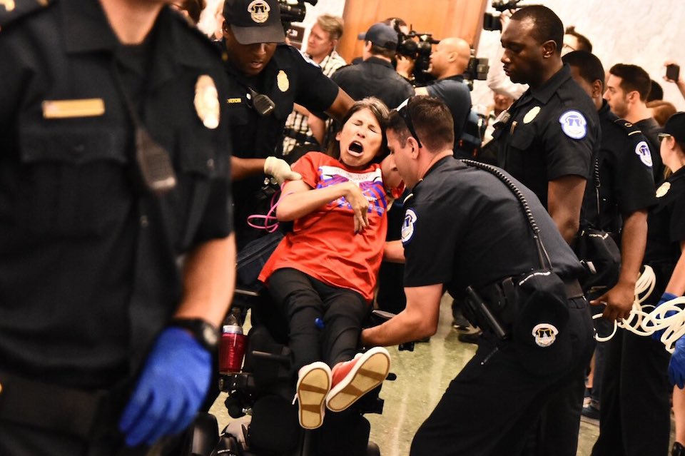 A disabled woman is carried out of the hearing room by police after protesting the Graham-Cassidy bill
