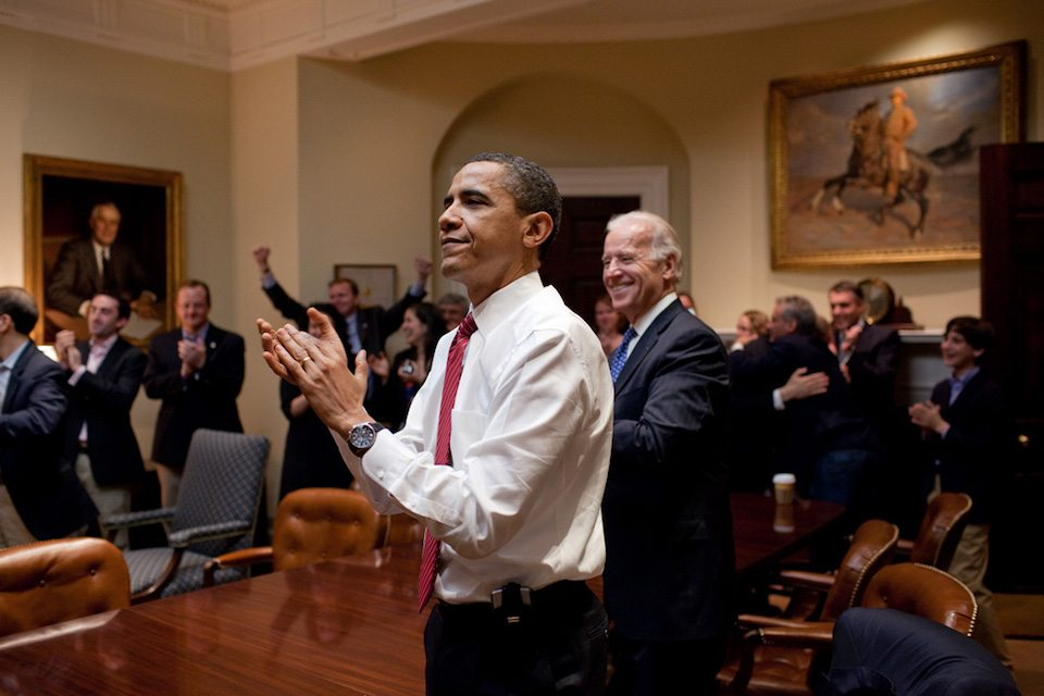 President Barack Obama, Vice President Joe Biden, and senior staff applaud in the Roosevelt Room of the White House, as the House passes the health care reform bill, March 21, 2010.