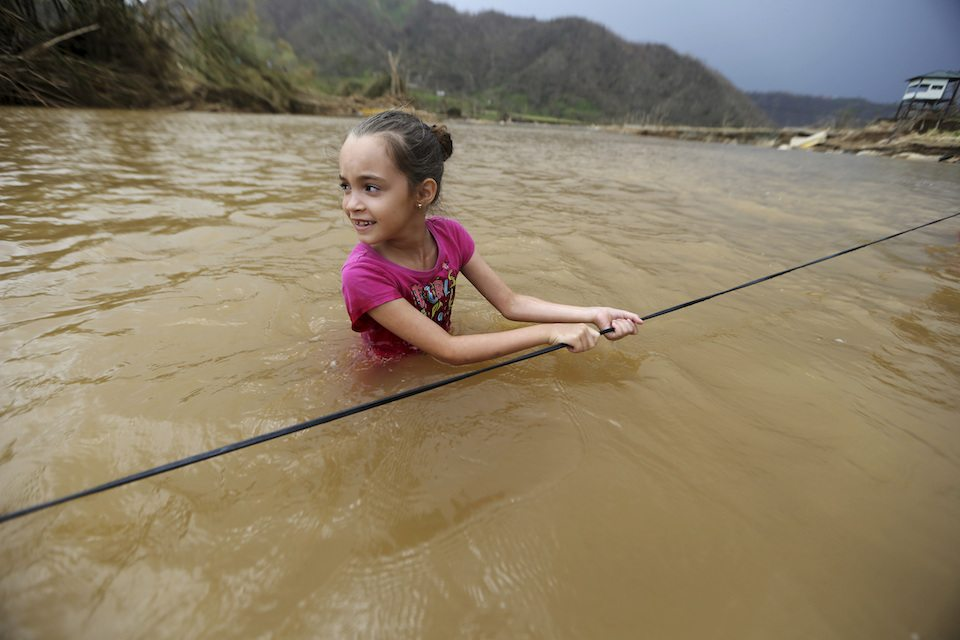 Ruby Rodriguez, 8, looks back at her mother as she wades across the San Lorenzo Morovis river with her family, since the bridge was swept away by Hurricane Maria