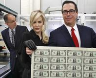 Treasury Secretary Steven Mnuchin, right, and his wife Louise Linton, hold up a sheet of new $1 bills
