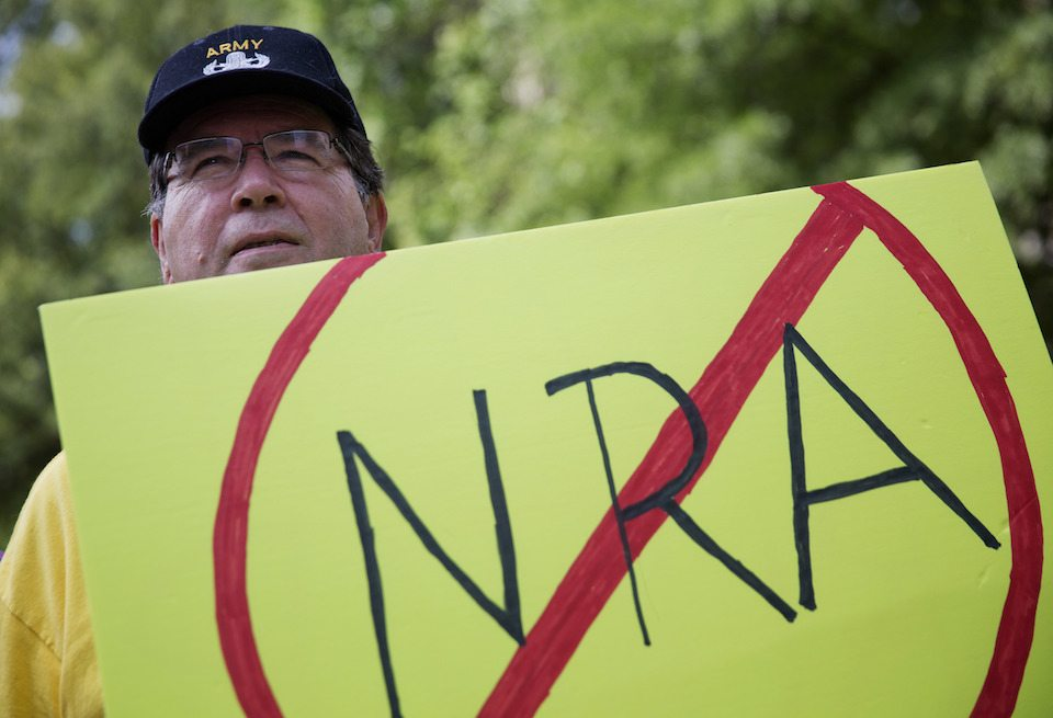 U.S. Army veteran Pax Riddle holds a sign during a rally protesting the National Rifle Association's annual convention