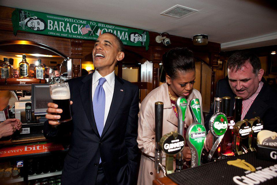 President Barack Obama talks with pub-goers as First Lady Michelle Obama draws a pint at Ollie Hayes pub in Moneygall, Ireland, May 23, 2011. (Official White House Photo by Pete Souza) This official White House photograph is being made available only for publication by news organizations and/or for personal use printing by the subject(s) of the photograph. The photograph may not be manipulated in any way and may not be used in commercial or political materials, advertisements, emails, products, promotions that in any way suggests approval or endorsement of the President, the First Family, or the White House.