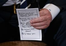 Donald Trump holds notes during a listening session with high school students and teachers