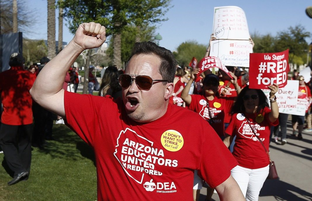 Arizona teachers and education advocates shout as they march at the Arizona Capitol highlighting low teacher pay and school funding