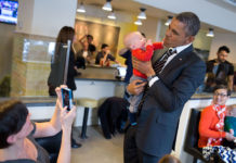 President Barack Obama holds a baby while greeting patrons at The Coupe restaurant in Washington, D.C.