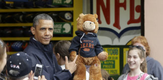 President Barack Obama holds up a stuffed bear that New Jersey Gov. Chris Christie, not shown, had won tossing a football after playing the 'Touchdown Fever' game on the boardwalk