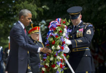 President Barack Obama and with the aid of Sgt. 1st Class John C. Wirth lays a wreath at the Tomb of the Unknowns, on Memorial Day, Monday, May 25, 2015, at Arlington National Cemetery