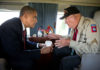 President Barack Obama talks with WWII veteran Kenneth (Rock) Merritt aboard Marine One after departing the 70th French-American Commemoration D-Day Ceremony at the Normandy American Cemetery and Memorial in Colleville-sur-Mer, France, June 6, 2014.
