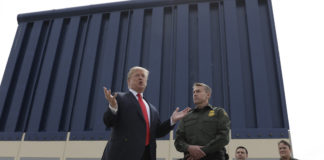 Donald Trump stands in front of a prototype of his racist border wall