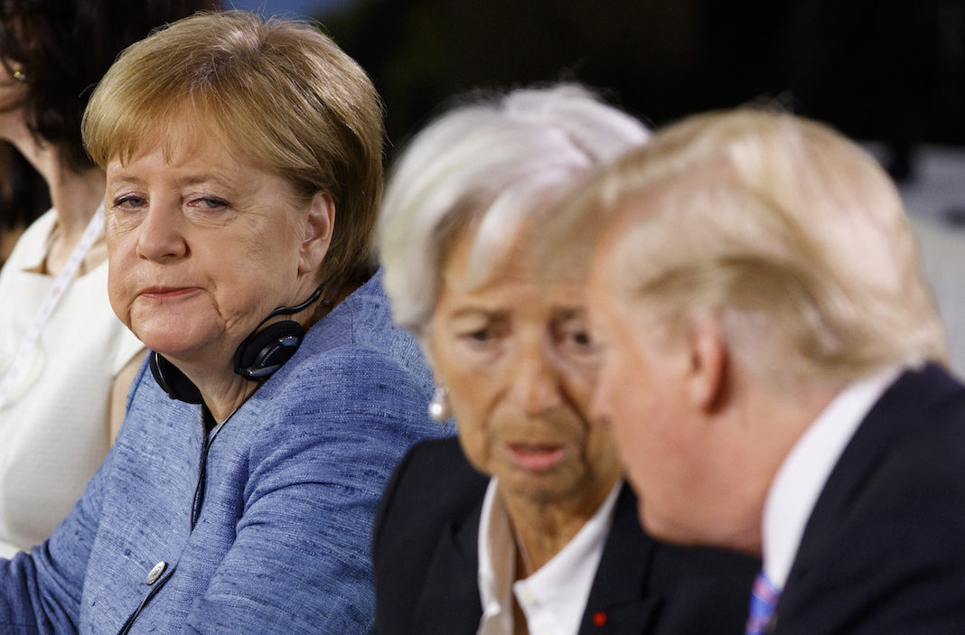 German Chancellor Angela Merkel watches as President Donald Trump talks with IMF Managing Director Christine Lagarde during the Gender Equality Advisory Council breakfast during the G-7 summit, Saturday, June 9, 2018, in Charlevoix, Canada.
