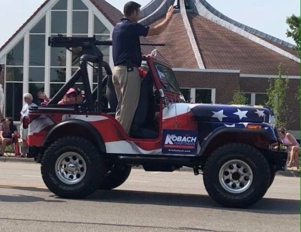 Kansas Republican Secretary of State Kris Kobach, also a candidate for governor, rides in a parade with a replica machine gun on his vehicle
