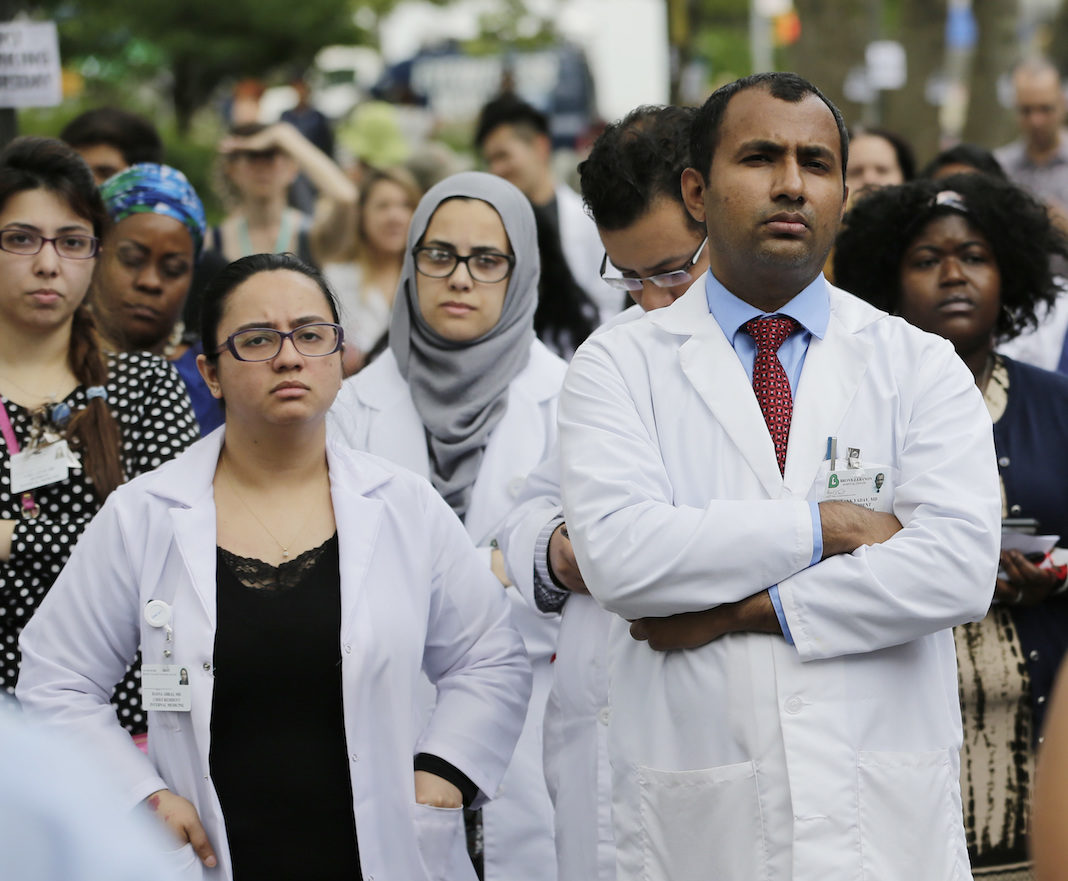 Hospital employees and others attend an anti-gun violence rally in front of the Bronx Lebanon Hospital Center in New York, Thursday, July 6, 2017. Dr. Tracy Sin-Yee Tam was fatally shot when Dr. Henry Bello opened fire at the hospital on June 30.