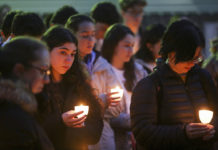 Students hold candles at a vigil.