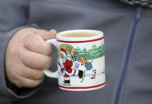 A man holds a Christmas-themed coffee mug.