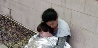 Immigrant mother and child sleeping on the ground at a McAllen, Texas border patrol station