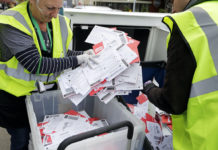 Election workers collect ballots.