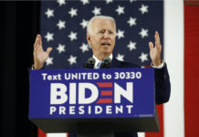 Joe Biden at podium with sign