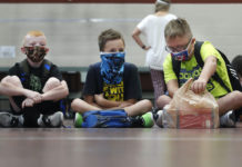 Kids sit crosslegged wearing masks in school