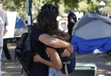 Couple hugging at a homeless camp.