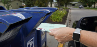 Voter putting ballot in mailbox