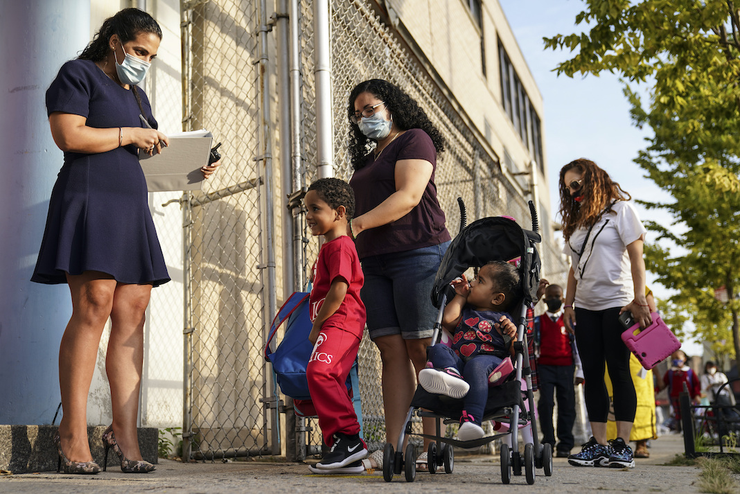 Masked teacher with parent and students in NYC