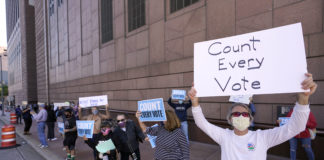 Protesters stand outside the federal courthouse in Houston, Texas, to call to count nearly 127,000 ballots from drive-thru polling places in Harris County.