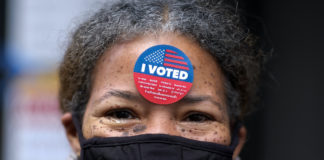 Woman with I Voted sticker on forehead