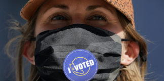 Woman in mask with I Voted sticker