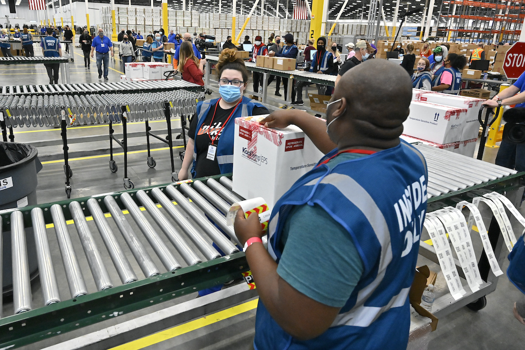 Warehouse workers load vaccines