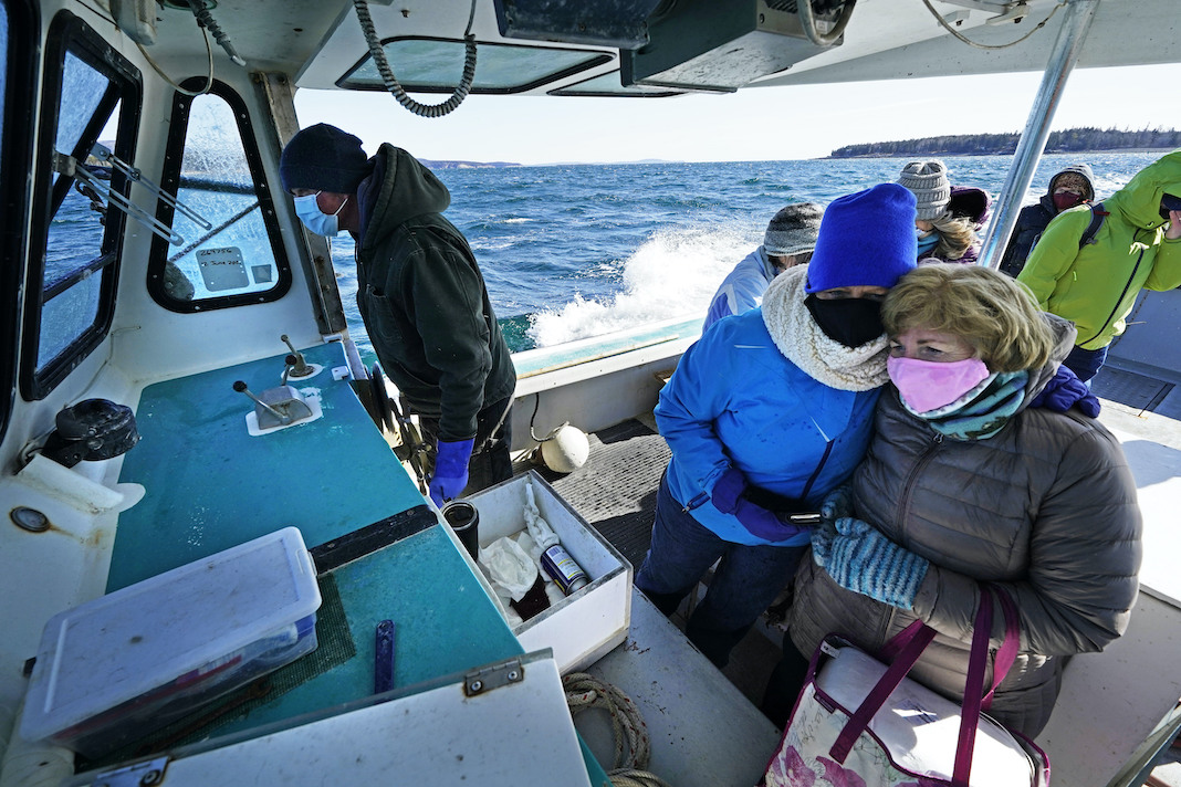 Nurses on a lobster boat delivering vaccines