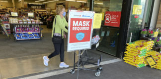Grocery store mask sign and shopper