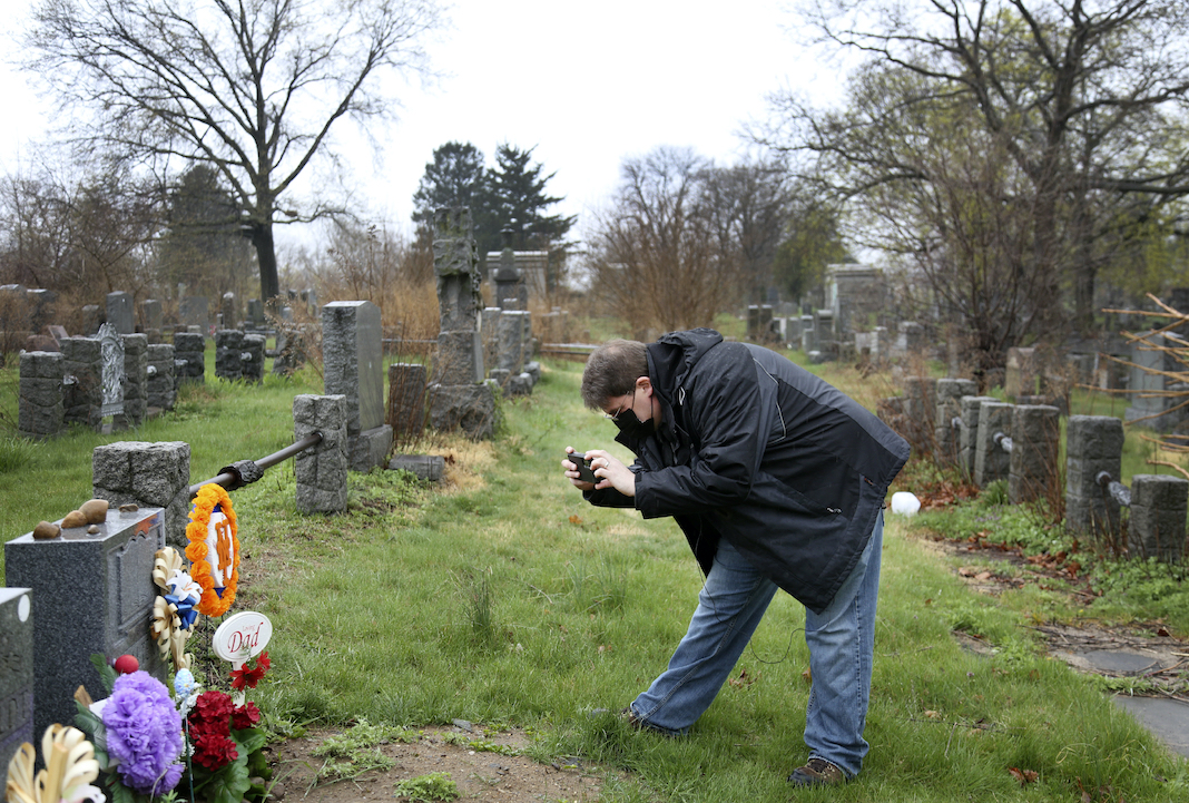 Son photographs his father's grave (COVID)