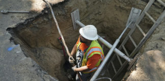 Worker removes lead pipe in Denver
