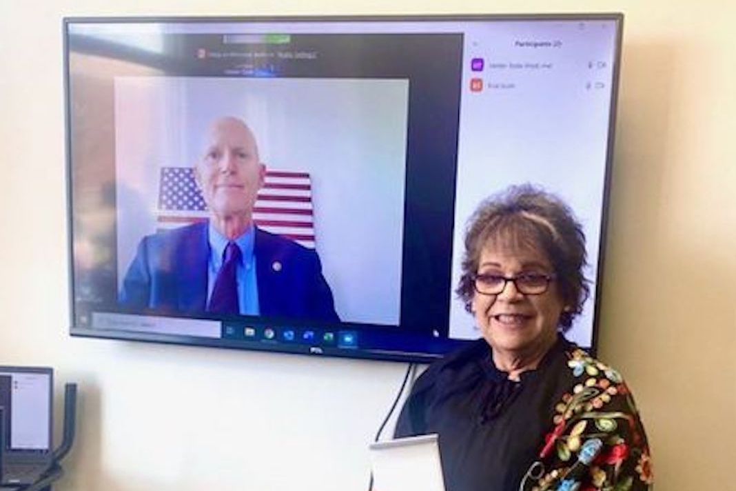 Maria Weese, with Rick Scott on screen